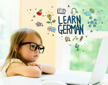 Learn German text with little girl using her laptop Stock Photo