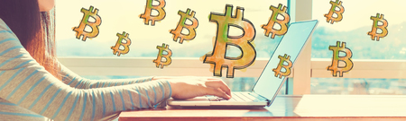 Bitcoin with woman working on a laptop in brightly lit room Stock fotó - 94803342