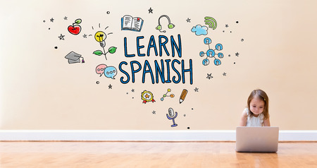 Learn Spanish text with little girl using a laptop computer on floor
