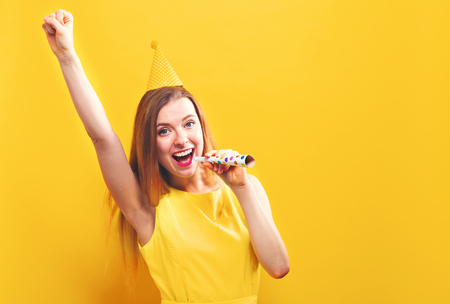 Young woman with party theme on a yellow background Stock Photo