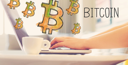Bitcoin with woman using a laptop in brightly lit room