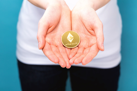 Woman holding a physical ethereum cryptocurrency coin in her hand