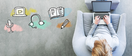 E-Learning with man using a laptop in a modern gray chair Standard-Bild