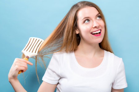 Beautiful woman holding a hairbrush on blue background 스톡 콘텐츠