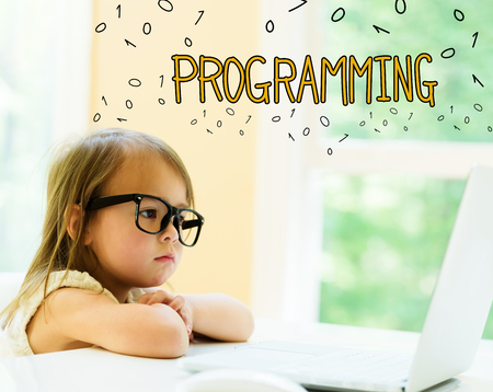 Programming text with little girl using her laptop Stock Photo