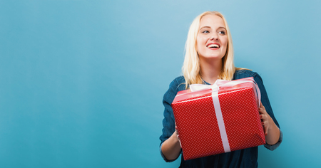 Happy young woman holding a gift box on a blue background Stock Photo