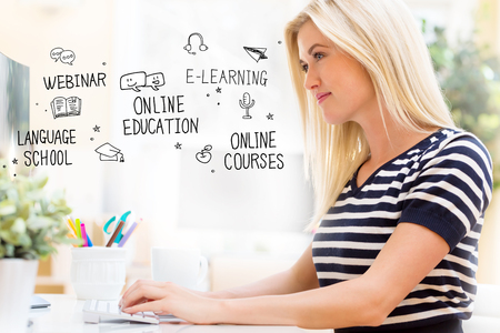 Online Education with happy young woman sitting at her desk in front of the computer Standard-Bild