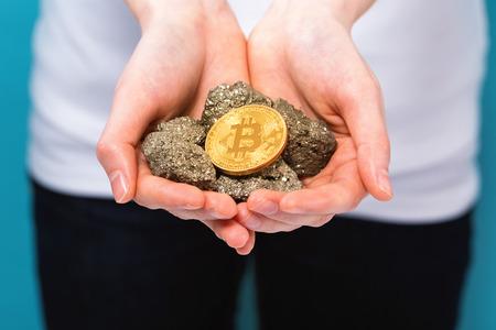 그녀의 손에 물리적 인 bitcoin cryptocurrency를 들고 여자
