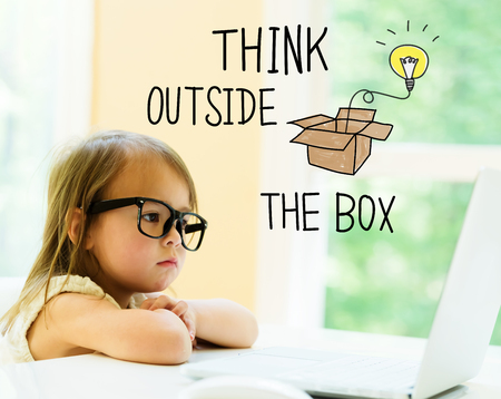 Think Outside The Box text with little girl using her laptop Stock Photo