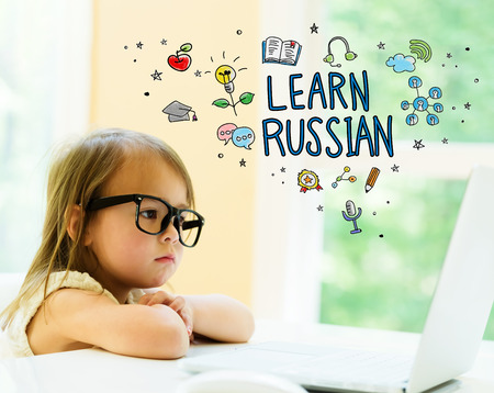 Learn Russian text with little girl using her laptop Stock Photo