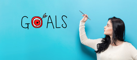 Goals with young woman holding a pen on a blue background Stock Photo