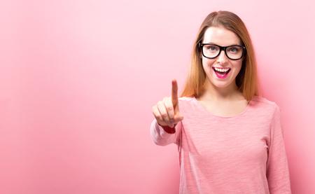Young woman pointing at something on a solid background Banco de Imagens - 95362991