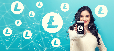 Litecoin with young woman holding out a smartphone in her hand Standard-Bild