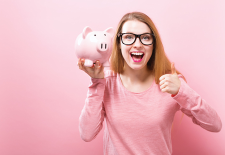 Young woman with a piggy bank on a solid background Zdjęcie Seryjne