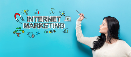 Internet Marketing with young woman holding a pen on a blue background Standard-Bild