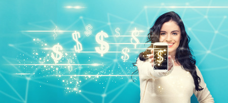 Dollars with young woman holding out a smartphone in her hand Standard-Bild