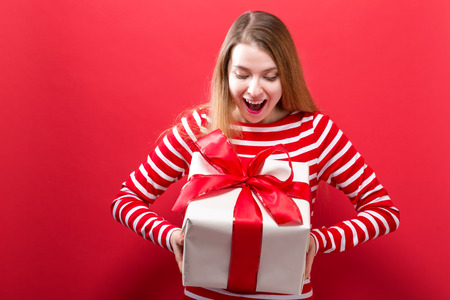 Happy young woman holding a gift box on a red background Standard-Bild