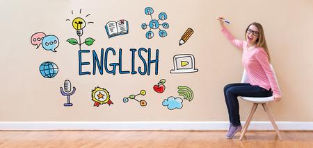 Inglés con joven mujer sosteniendo una pluma en una silla Foto de archivo - 95675093