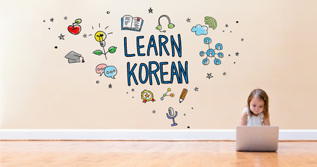 Learn Korean text with little girl using a laptop computer on floor Stock Photo