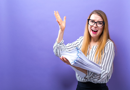 Office woman with a stack of documents on a solid background Stock Photo