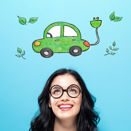 Electric Car with happy young woman on a blue background Stok Fotoğraf - 95899110