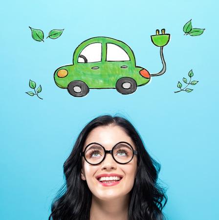 Elektroauto mit glücklichen jungen Frau auf einem blauen Hintergrund Standard-Bild - 95899110