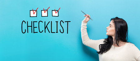 Checklist with young woman holding a pen on a blue background