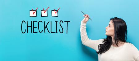 Liste de contrôle avec jeune femme tenant un stylo sur fond bleu Banque d'images - 95902074