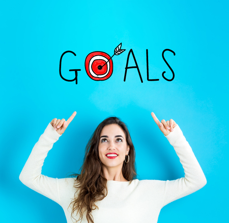 Goals with young woman reaching and looking upwards 写真素材