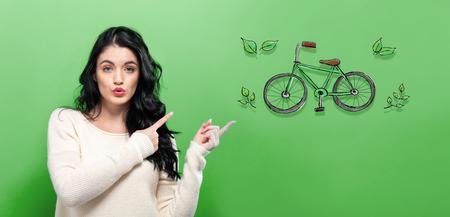 Bicicleta ecológica con mujer joven sobre un fondo verde