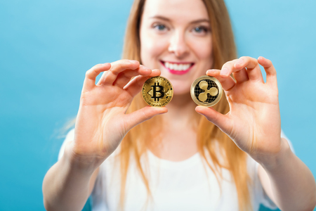 Woman holding physical bitcoin and ripple coins in her hands