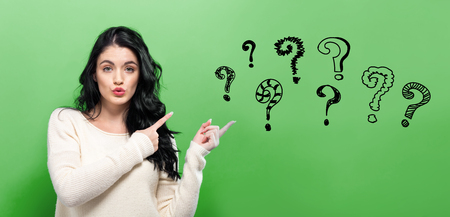Question Marks with young woman on a green background