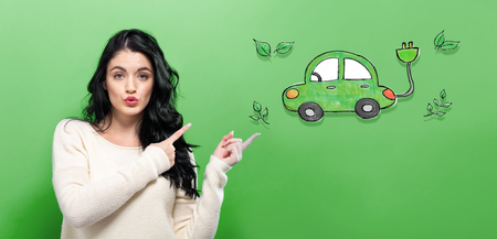 Electric Car with young woman on a green background