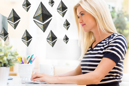 Ethereum with happy young woman sitting at her desk in front of the computer Stock Photo