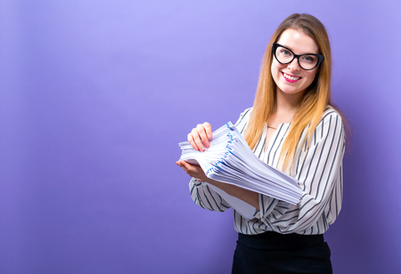 Office woman with a stack of documents on a solid background