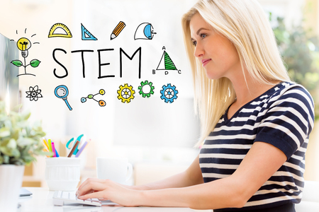 STEM with happy young woman sitting at her desk in front of the computer