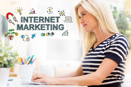 Internet Marketing with happy young woman sitting at her desk in front of the computer