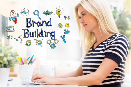 Brand Building with happy young woman sitting at her desk in front of the computer Stock Photo
