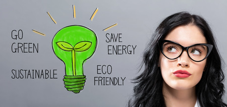 Green Light Bulb with young businesswoman in a thoughtful face