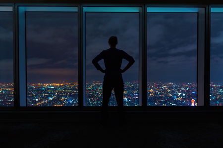 Man looking out large windows high above a sprawling city at night Banque d'images