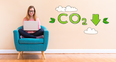 Reduce CO2 with young woman using her laptop in a chair Banco de Imagens