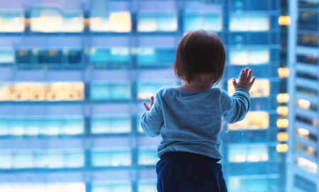 Toddler boy looking out the window in Tokyo, Japan