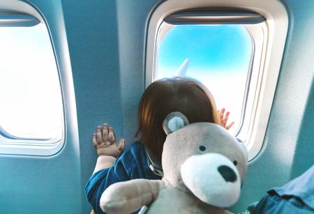 飛行中に飛行機の窓から外を見ている小さな幼児の少年
