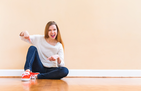 Happy young woman pointing to her shoes in a big open room
