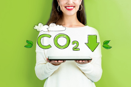 Reduce CO2 with woman holding a tablet computer Banco de Imagens