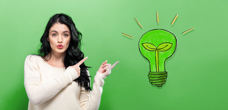 Eco Light Bulb with young woman on a green background