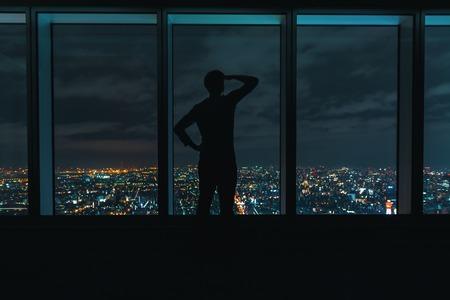 夜に広がる都市の上に大きな窓を見ている男