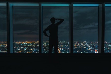 Man looking out large windows high above a sprawling city at night Stok Fotoğraf