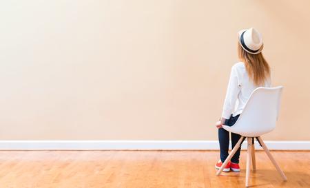 jeune femme assise dans une chaise en face d & # 39 ; un mur simple gros plan