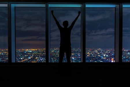 Man cheering while looking out large windows high above a sprawling city at night
